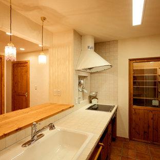 他の地域のシャビーシック調のおしゃれなペニンシュラキッチン (白いキッチンパネル、テラコッタタイルの床、白いキッチンカウンター、フラットパネル扉のキャビネット、中間色木目調キャビネット、タイルカウンター、茶色い床) の写真