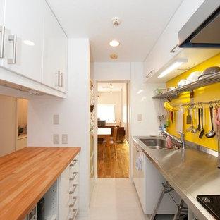 東京23区のインダストリアルスタイルのおしゃれなキッチン (シングルシンク、フラットパネル扉のキャビネット、白いキャビネット、ステンレスカウンター、黄色いキッチンパネル、グレーの床、茶色いキッチンカウンター) の写真