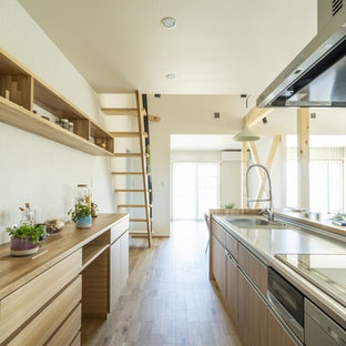 他の地域の中サイズのモダンスタイルのおしゃれなキッチン (一体型シンク、インセット扉のキャビネット、中間色木目調キャビネット、人工大理石カウンター、白いキッチンパネル、シルバーの調理設備の、淡色無垢フローリング、茶色い床、茶色いキッチンカウンター) の写真