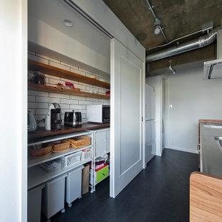 Idee per una piccola cucina industriale con lavello sottopiano, ante a filo, ante in legno scuro, top in acciaio inossidabile, paraspruzzi bianco, pavimento con piastrelle in ceramica, isola e pavimento nero