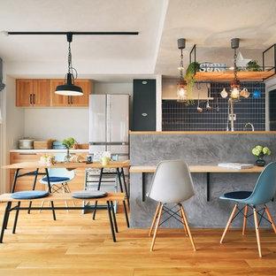他の地域のアジアンスタイルのおしゃれなキッチン (シェーカースタイル扉のキャビネット、中間色木目調キャビネット、黒いキッチンパネル、白い調理設備、無垢フローリング、茶色い床、白いキッチンカウンター) の写真