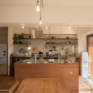 Photo of an eclectic galley eat-in kitchen in Tokyo with stainless steel benchtops, white splashback, subway tile splashback, with island, open cabinets, medium wood cabinets and medium hardwood floors.