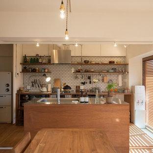 Zweizeilige Stilmix Wohnküche mit Edelstahl-Arbeitsplatte, Küchenrückwand in Weiß, Rückwand aus Metrofliesen, Kücheninsel, offenen Schränken, hellbraunen Holzschränken und braunem Holzboden in Tokio