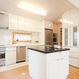 他の地域の大きい北欧スタイルのおしゃれなキッチン (一体型シンク、レイズドパネル扉のキャビネット、人工大理石カウンター、白いキッチンパネル、セラミックタイルのキッチンパネル、シルバーの調理設備の、テラコッタタイルの床、ベージュの床、マルチカラーのキッチンカウンター) の写真