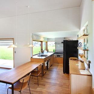 Idée de décoration pour une cuisine ouverte asiatique avec un sol en bois brun et un sol marron.