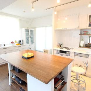 横浜の北欧スタイルのおしゃれなキッチン (シングルシンク、落し込みパネル扉のキャビネット、白いキャビネット、白いキッチンパネル、茶色い床) の写真