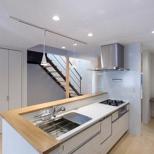 大阪のモダンスタイルのおしゃれなキッチン (シングルシンク、フラットパネル扉のキャビネット、白いキャビネット、淡色無垢フローリング、ベージュの床、茶色いキッチンカウンター) の写真