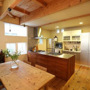他の地域のカントリー風おしゃれなキッチン (一体型シンク、ステンレスカウンター、茶色いキッチンパネル、木材のキッチンパネル、シルバーの調理設備の、無垢フローリング、茶色い床、フラットパネル扉のキャビネット、茶色いキャビネット、茶色いキッチンカウンター) の写真