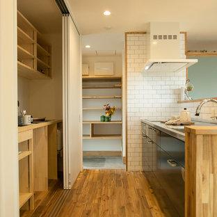 Inspiration pour une cuisine ouverte linéaire asiatique avec un plan de travail en inox, une crédence en carreau de porcelaine, un évier 1 bac, un placard à porte plane, des portes de placard noires, un sol en bois brun et un sol marron.