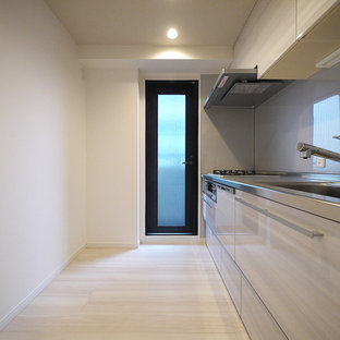 Inspiration for a modern single-wall enclosed kitchen in Tokyo with an integrated sink, grey splashback, stainless steel appliances, plywood flooring, an island and beige floors.