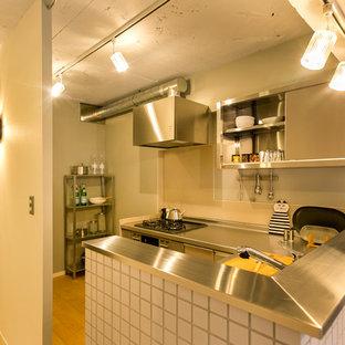 他の地域の小さい北欧スタイルのおしゃれなキッチン (フラットパネル扉のキャビネット、ステンレスキャビネット、ステンレスカウンター、淡色無垢フローリング、茶色い床) の写真