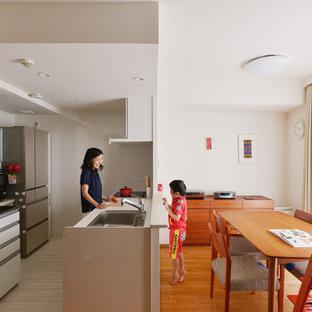 東京都下のコンテンポラリースタイルのおしゃれなキッチン (ドロップインシンク、フラットパネル扉のキャビネット、白いキッチンカウンター) の写真