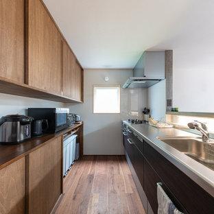 Cette image montre une grande cuisine parallèle asiatique avec un évier encastré, un placard à porte plane, des portes de placard en bois brun, un plan de travail en bois, un électroménager encastrable, un sol en bois brun, aucun îlot, un sol marron et un plan de travail marron.