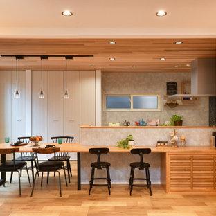 他の地域のアジアンスタイルのおしゃれなキッチン (フラットパネル扉のキャビネット、ベージュのキャビネット、無垢フローリング、茶色い床) の写真