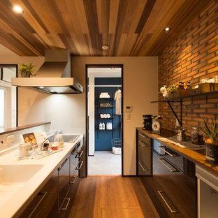 他の地域のアジアンスタイルのおしゃれなキッチン (一体型シンク、フラットパネル扉のキャビネット、茶色いキャビネット、白いキッチンパネル、無垢フローリング、茶色い床、茶色いキッチンカウンター) の写真