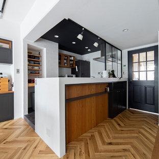 大阪のコンテンポラリースタイルのおしゃれなキッチン (コンクリートカウンター、白いキッチンパネル、黒い調理設備、ガラス扉のキャビネット、中間色木目調キャビネット、無垢フローリング、茶色い床、白いキッチンカウンター) の写真