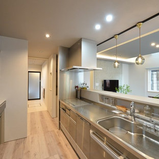 This is an example of a modern single-wall open plan kitchen in Other with an integrated sink, flat-panel cabinets, painted wood floors, a peninsula and beige floor.