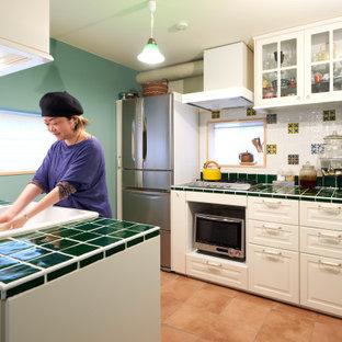 東京23区の中くらいのラスティックスタイルのおしゃれなキッチン (エプロンフロントシンク、インセット扉のキャビネット、白いキャビネット、タイルカウンター、白いキッチンパネル、モザイクタイルのキッチンパネル、シルバーの調理設備、テラコッタタイルの床、ベージュの床、緑のキッチンカウンター、塗装板張りの天井) の写真