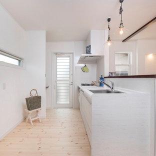 他の地域のカントリー風おしゃれなキッチン (シングルシンク、白いキャビネット、人工大理石カウンター、白いキッチンパネル、黒い調理設備、淡色無垢フローリング、白い床、フラットパネル扉のキャビネット、白いキッチンカウンター) の写真