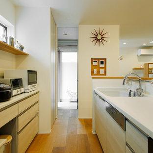 東京23区の中くらいの北欧スタイルのおしゃれなキッチン (一体型シンク、フラットパネル扉のキャビネット、淡色木目調キャビネット、人工大理石カウンター、白いキッチンパネル、セラミックタイルのキッチンパネル、白い調理設備、無垢フローリング、茶色い床、白いキッチンカウンター) の写真