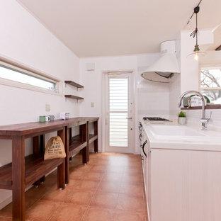 他の地域のカントリー風おしゃれなキッチン (インセット扉のキャビネット、淡色木目調キャビネット、人工大理石カウンター、ピンクのキッチンパネル、モザイクタイルのキッチンパネル、シングルシンク、黒い調理設備、テラコッタタイルの床、茶色い床、茶色いキッチンカウンター) の写真