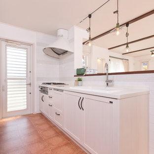 他の地域のカントリー風おしゃれなキッチン (シングルシンク、インセット扉のキャビネット、淡色木目調キャビネット、人工大理石カウンター、ピンクのキッチンパネル、黒い調理設備、テラコッタタイルの床、茶色い床、モザイクタイルのキッチンパネル) の写真
