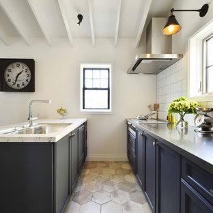 他の地域のミッドセンチュリースタイルのおしゃれなキッチン (シングルシンク、落し込みパネル扉のキャビネット、黒いキャビネット、ステンレスカウンター、白いキッチンパネル、グレーの床) の写真