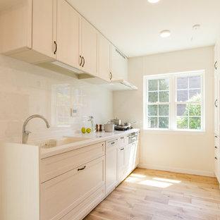 他の地域の大きいトラディショナルスタイルのおしゃれなキッチン (一体型シンク、シェーカースタイル扉のキャビネット、白いキャビネット、人工大理石カウンター、白いキッチンパネル、シルバーの調理設備の、無垢フローリング、アイランドなし、茶色い床、白いキッチンカウンター) の写真