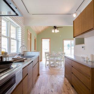 他の地域の中サイズのトロピカルスタイルのおしゃれなキッチン (一体型シンク、フラットパネル扉のキャビネット、濃色木目調キャビネット、ステンレスカウンター、白いキッチンパネル、セラミックタイルのキッチンパネル、シルバーの調理設備の、無垢フローリング、アイランドなし、茶色い床、グレーのキッチンカウンター) の写真