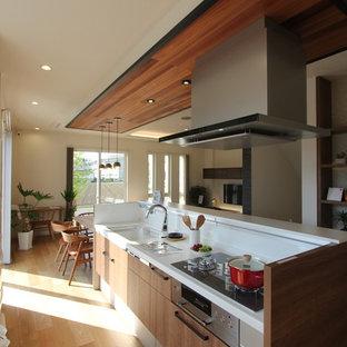 他の地域の広いラスティックスタイルのおしゃれなキッチン (一体型シンク、中間色木目調キャビネット、人工大理石カウンター、白い調理設備、淡色無垢フローリング、茶色い床、白いキッチンカウンター、フラットパネル扉のキャビネット、白いキッチンパネル) の写真