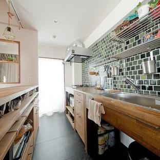 大阪のアジアンスタイルのおしゃれなキッチン (クッションフロア、黒い床、ベージュのキッチンカウンター、シングルシンク、フラットパネル扉のキャビネット、中間色木目調キャビネット、木材カウンター、緑のキッチンパネル) の写真