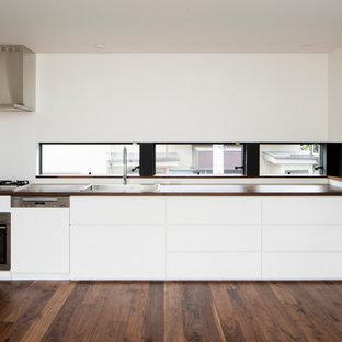東京23区のモダンスタイルのおしゃれなI型キッチン (ドロップインシンク、フラットパネル扉のキャビネット、白いキャビネット、白いキッチンパネル、シルバーの調理設備の、濃色無垢フローリング) の写真