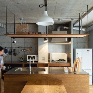 東京都下のインダストリアルスタイルのおしゃれなアイランドキッチン (一体型シンク、オープンシェルフ、中間色木目調キャビネット、ステンレスカウンター、無垢フローリング、茶色い床) の写真