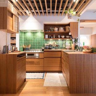 北欧スタイルのおしゃれなキッチン (シングルシンク、フラットパネル扉のキャビネット、中間色木目調キャビネット、木材カウンター、緑のキッチンパネル、無垢フローリング、茶色い床、茶色いキッチンカウンター) の写真