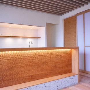 Offene, Einzeilige Küche mit weißen Schränken, Edelstahl-Arbeitsplatte, Küchenrückwand in Weiß und Kücheninsel in Sonstige