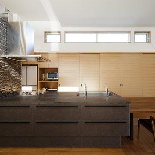他の地域のモダンスタイルのおしゃれなキッチン (シングルシンク、フラットパネル扉のキャビネット、茶色いキャビネット、無垢フローリング、茶色い床、茶色いキッチンカウンター) の写真