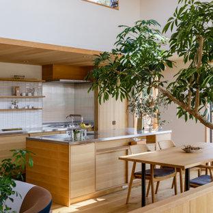 他の地域のアジアンスタイルのおしゃれなキッチン (一体型シンク、フラットパネル扉のキャビネット、中間色木目調キャビネット、ステンレスカウンター、白いキッチンパネル、モザイクタイルのキッチンパネル、無垢フローリング、茶色い床、グレーのキッチンカウンター) の写真