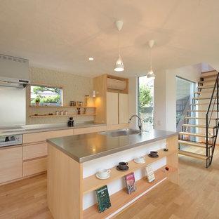 他の地域の北欧スタイルのおしゃれなキッチン (シングルシンク、フラットパネル扉のキャビネット、ステンレスカウンター、淡色無垢フローリング、ベージュの床、淡色木目調キャビネット、モザイクタイルのキッチンパネル、グレーのキッチンカウンター、パネルと同色の調理設備) の写真
