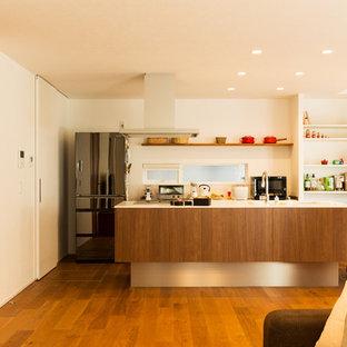 他の地域のモダンスタイルのおしゃれなキッチン (一体型シンク、フラットパネル扉のキャビネット、中間色木目調キャビネット、無垢フローリング、茶色い床、白いキッチンカウンター) の写真