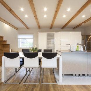 他の地域のコンテンポラリースタイルのおしゃれなキッチン (アンダーカウンターシンク、フラットパネル扉のキャビネット、白いキャビネット、ステンレスカウンター、白いキッチンパネル、シルバーの調理設備の、無垢フローリング、茶色い床、グレーのキッチンカウンター) の写真