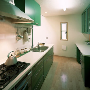 Small contemporary single-wall open plan kitchen in Tokyo with an undermount sink, flat-panel cabinets, green cabinets, solid surface benchtops, white splashback, slate splashback, stainless steel appliances, plywood floors, a peninsula, brown floor and white benchtop.
