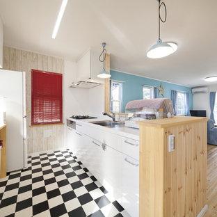 他の地域のビーチスタイルのおしゃれなキッチン (シングルシンク、フラットパネル扉のキャビネット、白いキャビネット、マルチカラーの床、茶色いキッチンカウンター) の写真