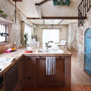 他の地域の地中海スタイルのおしゃれなキッチン (ドロップインシンク、落し込みパネル扉のキャビネット、タイルカウンター、テラコッタタイルの床、茶色い床) の写真