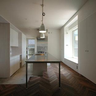 京都の北欧スタイルのおしゃれなキッチン (一体型シンク、フラットパネル扉のキャビネット、白いキャビネット、ステンレスカウンター、メタリックのキッチンパネル、シルバーの調理設備の、コンクリートの床) の写真