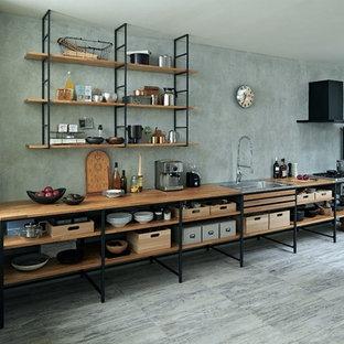 他の地域のインダストリアルスタイルのおしゃれなキッチン (シングルシンク、オープンシェルフ、木材カウンター、グレーのキッチンパネル、黒い調理設備、グレーの床) の写真