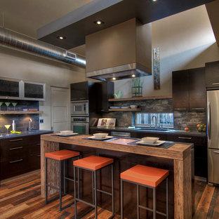 他の地域のコンテンポラリースタイルのおしゃれなキッチン (濃色木目調キャビネット、アンダーカウンターシンク、フラットパネル扉のキャビネット、グレーのキッチンパネル、シルバーの調理設備の、濃色無垢フローリング) の写真