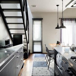 東京23区のインダストリアルスタイルのおしゃれなキッチン (アンダーカウンターシンク、インセット扉のキャビネット、グレーのキャビネット、ステンレスカウンター、無垢フローリング、茶色い床) の写真