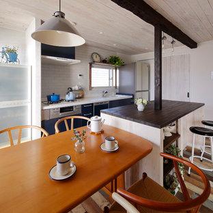 他の地域の北欧スタイルのおしゃれなキッチン (一体型シンク、白いキッチンパネル、塗装フローリング、マルチカラーの床) の写真