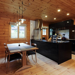 Asian open concept kitchen ideas - Open concept kitchen - zen single-wall light wood floor and brown floor open concept kitchen idea with a single-bowl sink, flat-panel cabinets, black cabinets and a peninsula