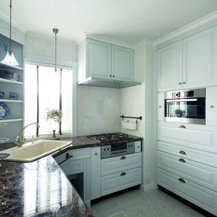 横浜のトラディショナルスタイルのおしゃれなキッチン (ドロップインシンク、フラットパネル扉のキャビネット、青いキャビネット、大理石カウンター、青いキッチンパネル、パネルと同色の調理設備) の写真
